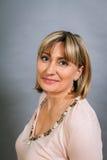 Lächelnde überzeugte blonde Frau von mittlerem Alter Lizenzfreies Stockfoto