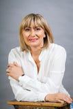 Lächelnde überzeugte blonde Frau von mittlerem Alter Stockbild