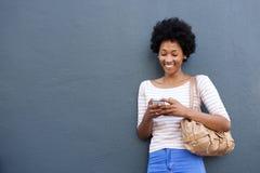 Lächelnde afrikanische Frau mit der Tasche, die Handy betrachtet Lizenzfreie Stockbilder