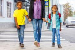 Lächelnde afrikanische Kinder mit Frau gehen auf die Straße Stockfoto