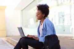 Lächelnde afrikanische Studentin der Seitenansicht, die auf Bürgersteig mit Laptop sitzt lizenzfreie stockfotos