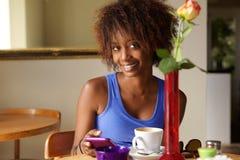 Lächelnde Afroamerikanerfrau, die Mobiltelefon am Café verwendet Stockbild