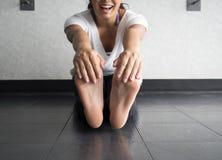 Lächelnde aktive Frau, die ihre Füße ergreift, um Kniesehnen im Studio auszudehnen lizenzfreie stockbilder