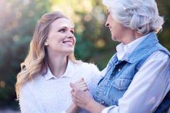 Lächelnde Alternfrau und reifen die Tochter, die in den Park geht Stockfoto
