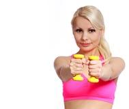 Lächelnde anhebende Dummköpfe der Eignungsfrau. blonde anhebende Gewichte der jungen Frau, lokalisiert Stockfotos