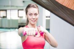 Lächelnde anhebende Gewichte der Frau in der Turnhalle Stockfotos