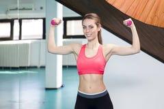Lächelnde anhebende Gewichte der Frau in der Turnhalle Lizenzfreies Stockbild