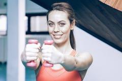 Lächelnde anhebende Gewichte der Frau in der Turnhalle Lizenzfreie Stockfotografie