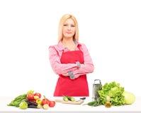 Lächelnde Arbeitnehmerin mit dem Schutzblech, das Salat zubereitet stockfotografie