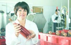 Lächelnde Arbeitnehmerinverpackungs-Weinflaschen Stockfotos