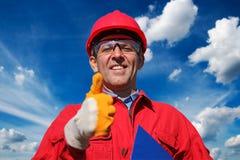 Lächelnde Arbeitskraft über blauer Himmel-und Wolken-Hintergrund stockfotos