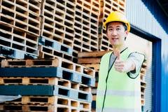 Lächelnde Arbeitskraft der industriellen Logistik mit hartem Sturzhelm in den Anlagen mit den Daumen oben lizenzfreie stockfotos