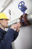 Lächelnde Arbeitskraft, welche die Ölpipelineausrüstung in einer Gasanlage, Peking, China überprüft lizenzfreies stockfoto
