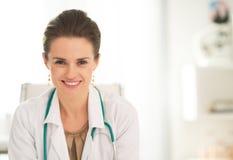 Lächelnde Arztfrau, die im Büro sitzt Lizenzfreie Stockfotografie