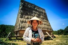 Lächelnde Asiatin gegen altes Haus mit hohem Reed Roof Stockfotografie