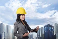 Lächelnde asiatische Auftragnehmerfrau mit dem gelben Sturzhelm, der clipbo hält stockfoto