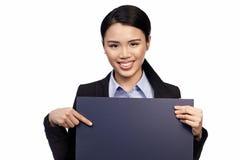 Lächelnde asiatische Dame mit unbelegtem Zeichen stockbild