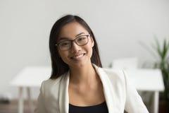Lächelnde asiatische Frau in den Gläsern, die Kamera, Headshot portr betrachten stockfotografie