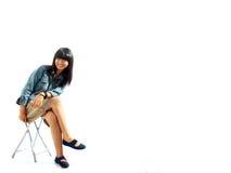 Lächelnde asiatische Frau, die auf Stuhl sitzt Stockbild