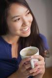 Lächelnde asiatische Frau, die den Becher Kaffee weg schauend hält Stockbilder