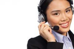 Lächelnde asiatische Frau, die einen Kopfhörer trägt lizenzfreie stockbilder