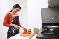 Lächelnde asiatische Frau, die Messer verwendet, um Pfeffer und das Kochen zu schneiden Stockbild