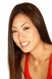 Lächelnde asiatische Frau, welche die Kamera betrachtet Stockbilder