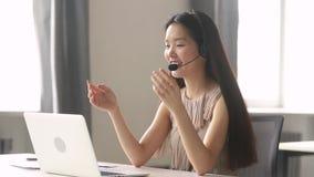 Lächelnde asiatische Geschäftsfrau, die das drahtlose Kopfhörervideo ersucht um Laptop trägt stock footage