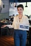 Lächelnde asiatische Kellnerin, die Willkommensschild zeigt lizenzfreies stockbild
