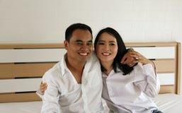 Lächelnde asiatische Paare, die auf dem Bett sich halten Stockfotografie