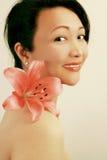 Lächelnde asiatische Schönheit mit Lilie Lizenzfreie Stockfotografie