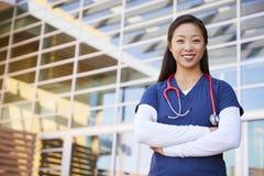 Lächelnde asiatische weibliche Gesundheitswesenarbeitskraft mit den Armen gekreuzt lizenzfreie stockbilder