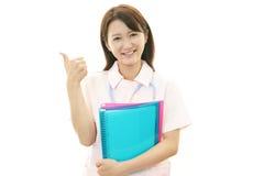 Lächelnde asiatische weibliche Krankenschwester mit den Daumen oben Lizenzfreie Stockbilder
