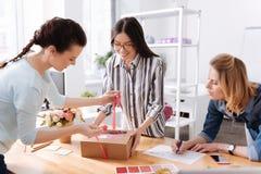 Lächelnde Atelierarbeitskräfte, die herauf einen Kasten binden stockbild