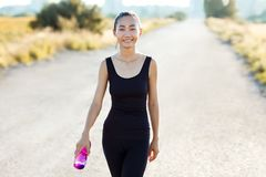 Lächelnde athletische Frau, die auf Landstraße- und Tragenwasser geht Stockbilder