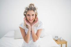 Lächelnde attraktive blonde tragende Haarlockenwickleraufstellung Stockfoto