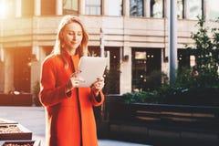 Lächelnde attraktive Frau der Junge im orange Mantel steht auf Stadtstraße und benutzt Tablet-Computer Mädchen, das E-Mail überpr Stockbild