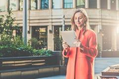Lächelnde attraktive Frau der Junge im orange Mantel steht auf Stadtstraße und benutzt Tablet-Computer Mädchen, das E-Mail überpr Lizenzfreie Stockfotografie