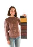 Lächelnde attraktive Frau in der Strickjacke, die Gewebemuster hält Stockbild