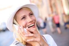 Lächelnde attraktive Frau, die auf dem Smartphone im Freien spricht Stockfotos