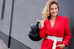 lächelnde attraktive Frau im roten Jackenholding-Motorradsturzhelm stockfotos