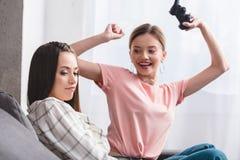 lächelnde attraktive Frau mit Steuerknüppel Sieg im Videospiel und in ihrem umgekippten Freundinsitzen feiernd stockfotografie