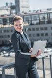 lächelnde attraktive Geschäftsfraustellung mit Laptop auf Brücke und dem Schauen stockbild