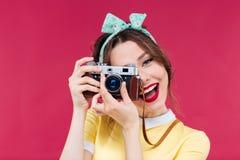 Lächelnde attraktive junge Frau, die Fotos unter Verwendung der alten Kamera macht Lizenzfreie Stockfotos