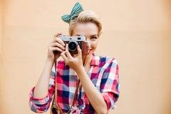 Lächelnde attraktive junge Frau, die Fotos unter Verwendung der alten Kamera macht Lizenzfreies Stockfoto