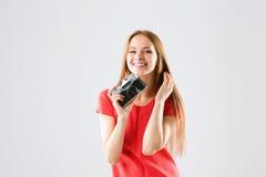 Lächelnde attraktive junge Frau, die Fotos unter Verwendung der alten Kamera macht Stockbilder