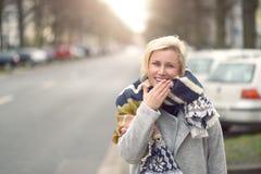 Lächelnde attraktive junge Frau in einem wolligen Schal Stockfotos