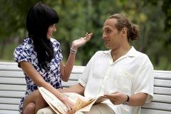Lächelnde attraktive Paarsitzung im Sommerpark stockfotografie