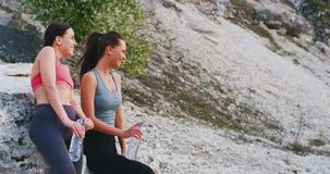 Lächelnde attraktive zwei junge Frauen, welche zusammen die Zeit mitten in Natur nach dem Sportprogramm sie genießen stock video
