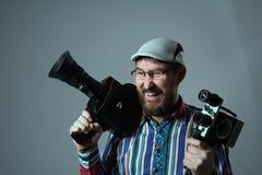 Lächelnde bärtige alte Retro- Filmkamera des Mannes zwei Lizenzfreie Stockbilder